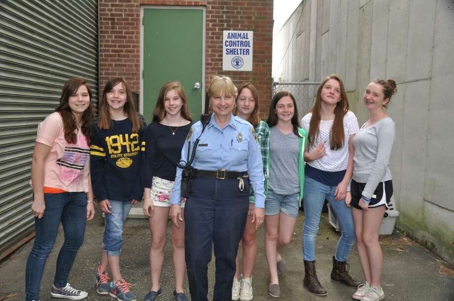 Girl Scout Troop 50198 recently visited New Canaan's animal shelter. From left, Amanda Hill, Celia Sokolowski, Katie Unger, Animal Control Officer Maryann Kleinschmitt, Emily Gaeta, Caroline Cioffi, Ellen Nelson and Allison Beck. Photo: Contributed Photo, Contributed / New Canaan News Contributed