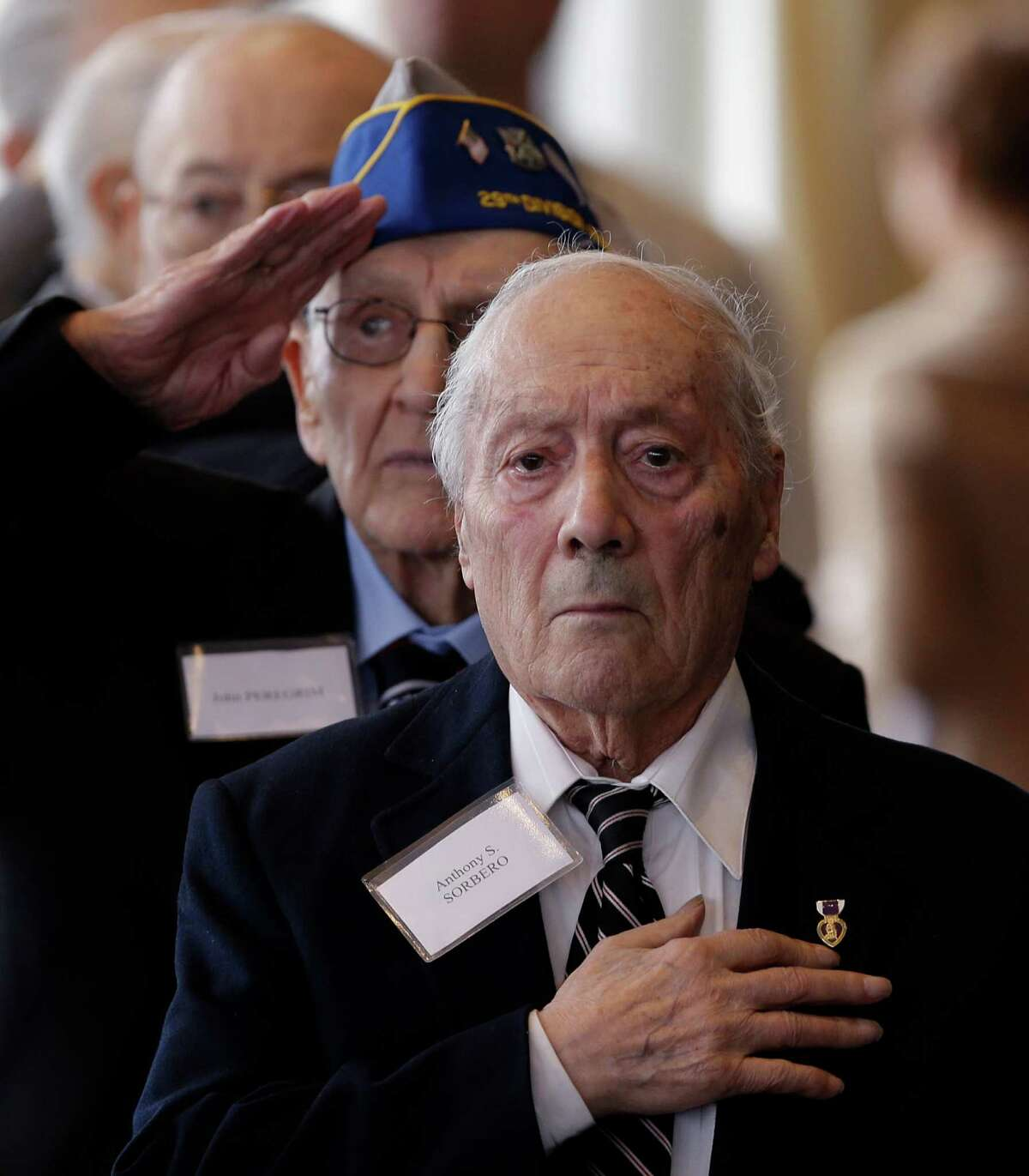 World War II veterans Anthony Sorbero of Amsterdam, N.Y., front, and John Peregrim of Devon, Conn., stand for the national anthems of France and the United States before being presented with the insignia of the French Legion of Honor during a ceremony at the U.S. Military Academy on Friday, May 9, 2014, in West Point, N.Y. Thirty-four U.S. veterans were honored 70 years after of the D-Day landings. (AP Photo/Mike Groll)1 ORG XMIT: NYMG101