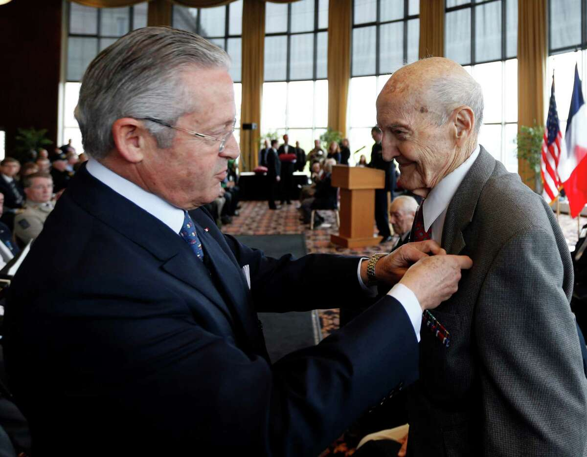 Guy Wildenstein, president of the American Society of the French Legion of Honor, left, presents an the legion's insignia to World War II veteran Francis Cocca of Green Island, N.Y., during a ceremony at the U.S. Military Academy on Friday, May 9, 2014, in West Point, N.Y. Thirty-four veterans were honored 70 years after of the D-Day landings. (AP Photo/Mike Groll) ORG XMIT: NYMG107