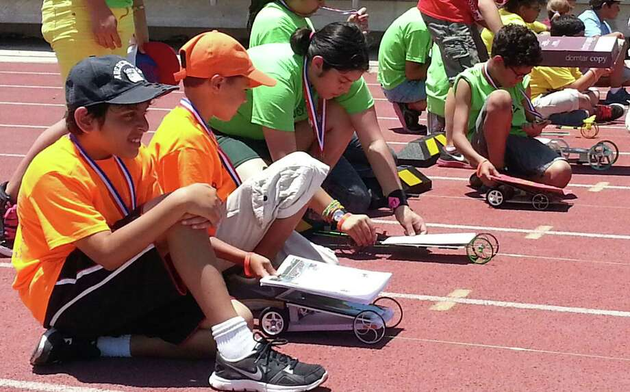 Athar Vadatta Wade, far left, and Joshua Montemayor of Beard Elementary prep their car during the semifinals of the Texas Solar Race Car event at Gustafson Stadium Saturday. Photo: Photos By Jeremy Gerlach / Stone Oak Weekly