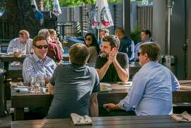 People enjoy happy hour on the patio at Stein's Beer Garden in Mountain View, Calif., on Tuesday, May 6th, 2014.