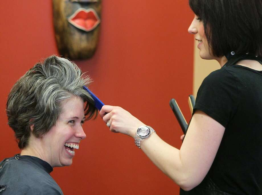 Natural look:Stylist Katie Guinan works on the graying locks of 34-year-old Michelle Touve-Holland, at Gavin Scott Salon and Spa in Stow, Ohio. Unlike most women, Touve-Holland has decided to keep her gray hair instead of coloring it. Photo: Mike Cardew, McClatchy-Tribune News Service