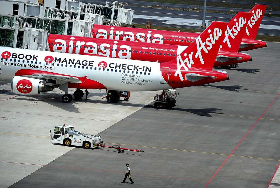 FILE - In this Friday, May 9, 2014 file photo, a ground crewman walks by a fleet of AirAsia's passenger jets on the tarmac of the new low cost terminal KLIA2 in Sepang, Malaysia, as AirAsia began its full operations from the new terminal on the day. The top Asian budget carrier said Tuesday, May 13, it will become the world's first airline to check the passports of all its passengers against Interpol's global database of 42 million stolen or lost travel documents by end of this month. (AP Photo/Joshua Paul, File) Photo: Joshua Paul, Associated Press