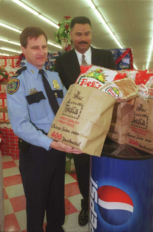CONTACT FILED:  HUNGER-HOUSTON Capt. Mark Fougerousse of the HPD Community Services Division, and HPD Chief Clarence Bradford help kick off the Comida Food Drive at a press conference at the Fiesta Food Mart, 4711 Airline, on 11/29/99.  The food drive is sponsored by the Houston Police Citizens' Academy Alunmi Association, Fiesta Inc., and Pepsi Co., with the assistance of the Houston Police Department.  Volunteers will man  food dropoff barrels at ten to thirteen Fiesta stores during the first two full weekends in December and the food will be distributed by local churches to the needy.  Photo by Betty Tichich. Photo: Betty Tichich, Staff / Houston Chronicle