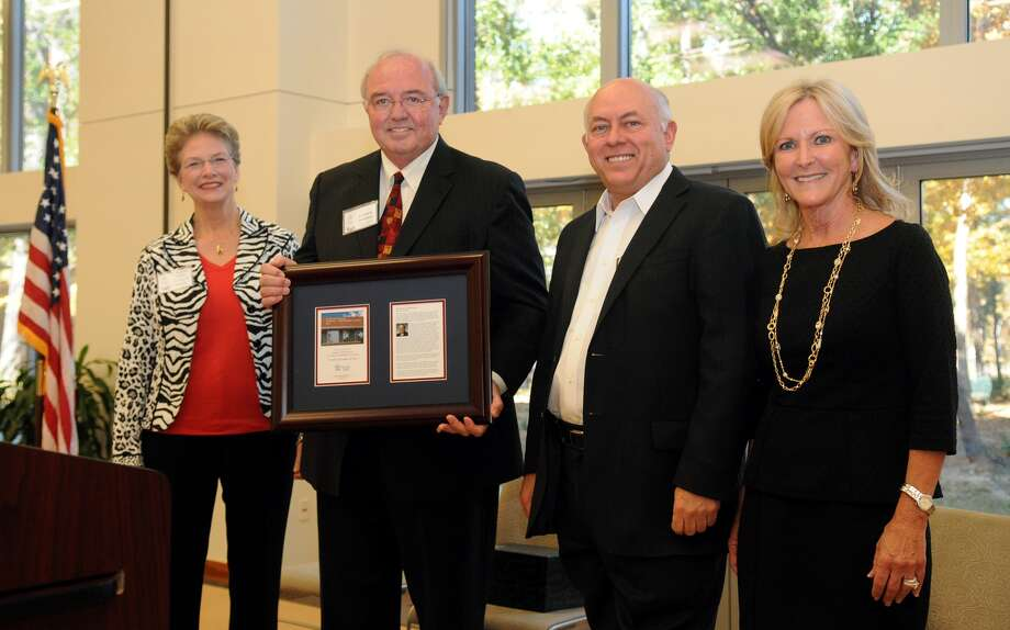 Richard Carpenter, second from right, PH.D. and Chancellor of Lone Star College, with Katherine Persson, left, Ph.D. and President of Lone Star College - Kingwood, and Stephanie Marquard, right, LSC-Kingwood Board of Trustee, make a special presentation to the guest of honor, John Pickelman, Ph.D., during the dedication ceremony of the John E. Pickelman Student Conference Center at LSC - Kingwood on Dec. 10. Photo: Jerry Baker, Freelance