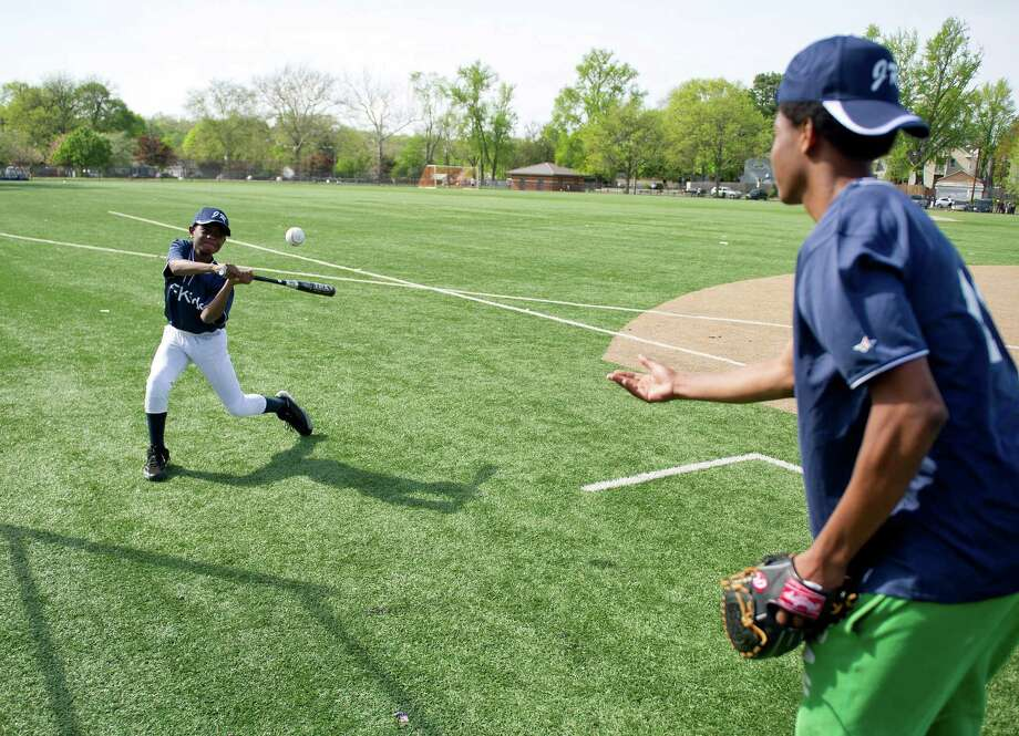 AFKids team assistant coach Patrick Dorcile throws balls to Tyrrese Bazile, 10, to practice batting before the Jackie Robinson Baseball League Opening Day ceremony at Lione Park in Stamford, Conn., on May 13, 2014. Photo: Lindsay Perry / Stamford Advocate