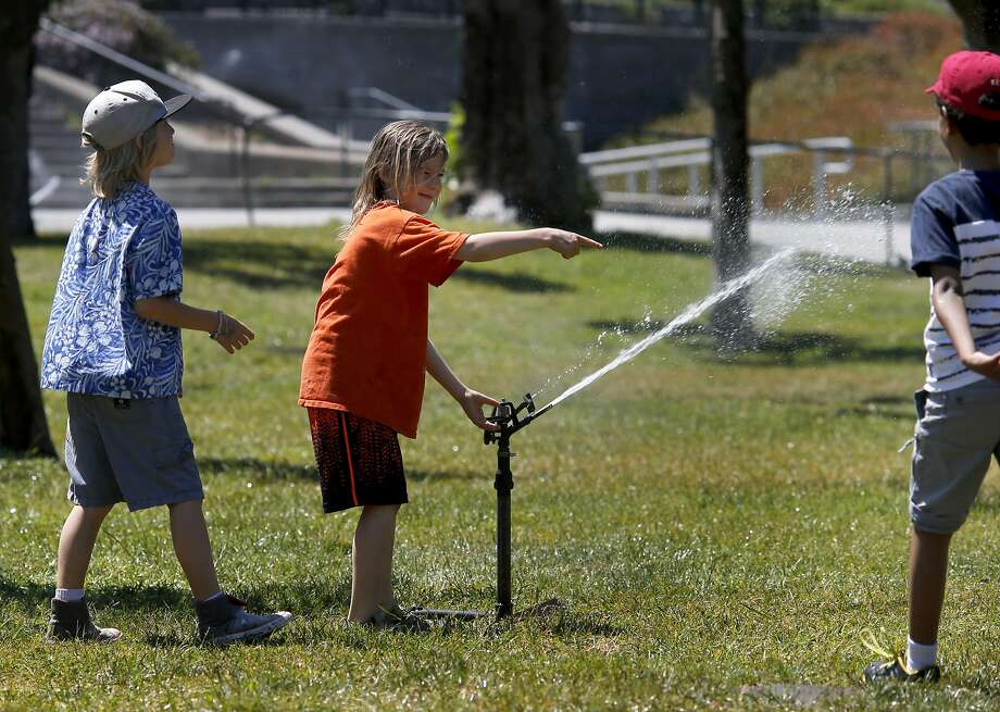 Three boys played with a sprinkler head in the park area in front of the California Academy of Sciences Tuesday May 13, 2014 in San Francisco, Calif. Hot weather returned to the Bay Area and visitors to Golden Gate park did their best to stay cool. Photo: Brant Ward, The Chronicle