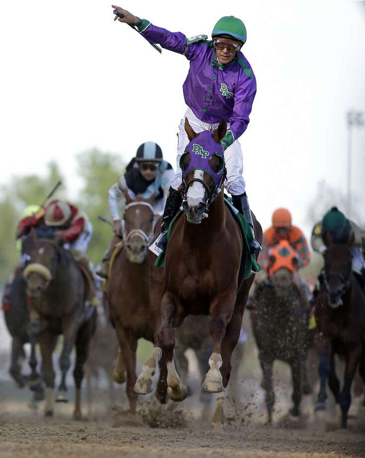 FILE - In this May 3, 2014, file photo, jockey Victor Espinoza celebrates aboard California Chrome after winning the 140th running of the Kentucky Derby horse race at Churchill Downs in Louisville, Ky. The California colt will be running in the Preakness with a bulls-eye on his back as perhaps racing's next superstar. He figures to face eight or nine rivals in the middle leg of the Triple Crown series, and one of them might be a filly.  (AP Photo/David J. Phillip, File) Photo: David J. Phillip, Associated Press