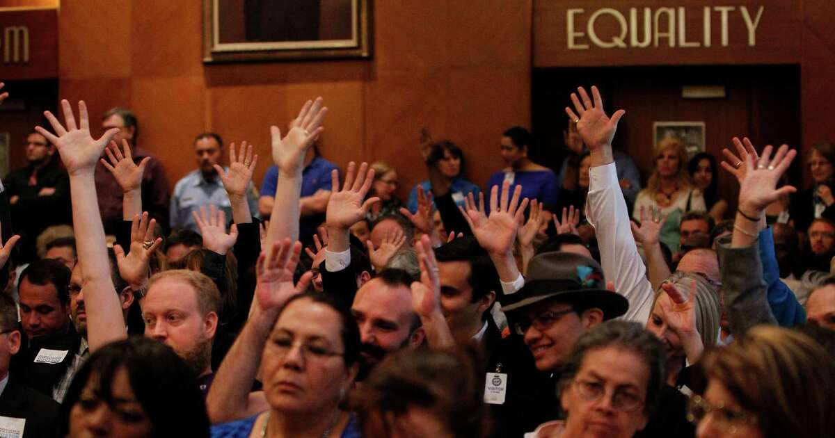 A capacity crowd waves their hands as they agree with a speaker on an issue as the proposed Equal Rights Ordinance was up for public discussion in front of city council members at City Hall, Wednesday, April 30, 2014, in Houston. ( Karen Warren / Houston Chronicle )