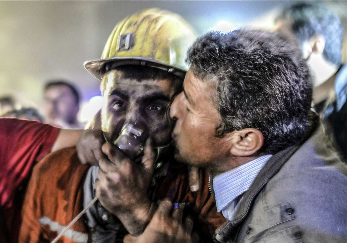 A father kisses his son, who was rescued Tuesday after an explosion in a coal mine in Soma, Turkey.