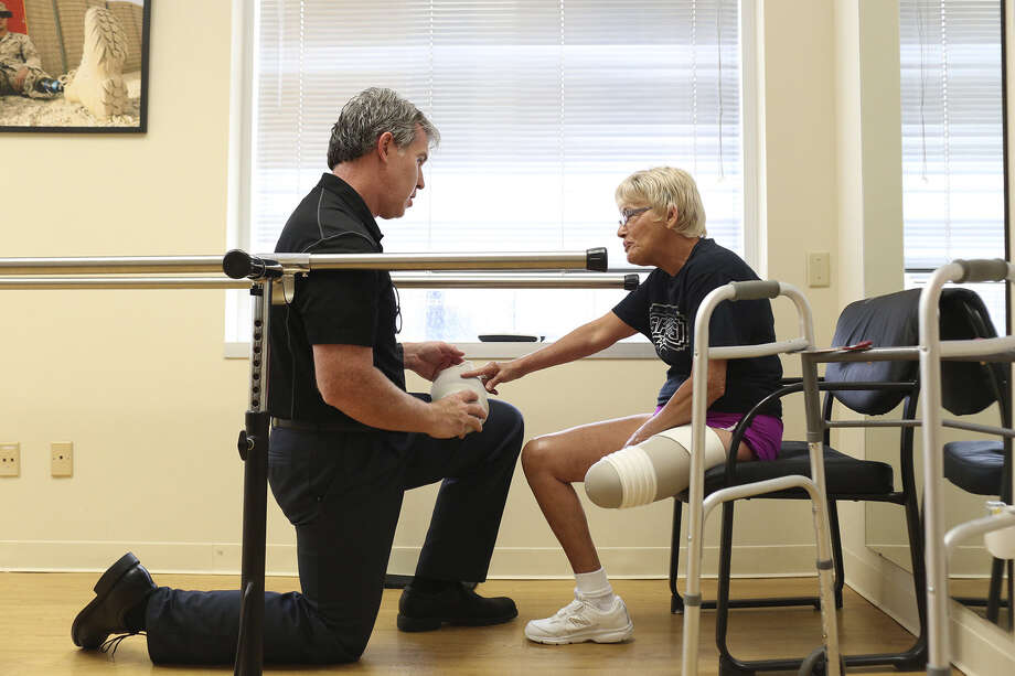 Prosthetist/Orthotist Kirk Simendinger talks with patient Alma Bryand about the liner for her prosthetic leg as he works at Bulow Orthotic & Prosthetic Solutions, but he says listening is what he does best. Photo: Lisa Krantz / San Antonio Express-News / SAN ANTONIO EXPRESS-NEWS