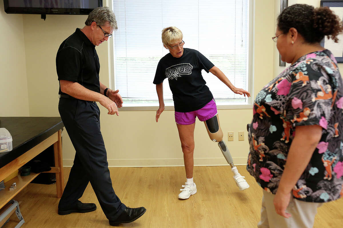 Prosthetist/Orthotist Kirk Simendinger shows patient Alma Bryand the best way to walk down a incline with her prosthetic leg as she loses her balance for a moment at Bulow Orthotic & Prosthetic Solutions in San Antonio on Monday, May 12, 2014. Office administrator Brenda Martinez, right, watches while helping with some translating.