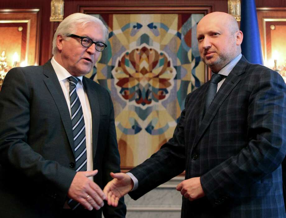 German Foreign Minister Frank-Walter Steinmeier, left, shakes hands with acting Ukrainian President Oleksandr Turchynov during a meeting in Kiev, Ukraine, Tuesday, May 13, 2014. Steinmeier flew to Ukraine Tuesday to help start talks between the Ukrainian government and its foes following the declaration of independence by two eastern region. (AP Photo/Sergei Chuzavkov) Photo: Sergei Chuzavkov, STF / AP