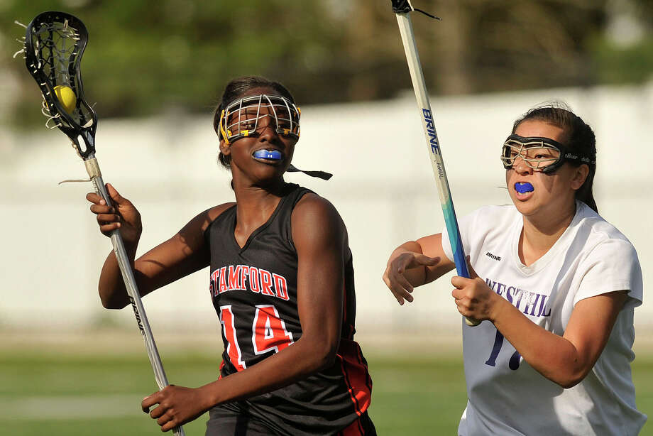 Stamford's Camry Evans runs the ball down the field while under pressure from Westhill's Sara Martelli during their lacrosse game at Westhill High School in Stamford, Conn., on Tuesday, May 13, 2014. Stamford won, 18-2. Photo: Jason Rearick / Stamford Advocate