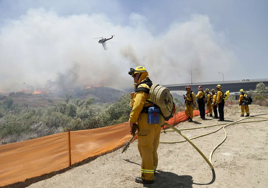 Firefighters watch from a ridge as a helicopter drops retardant on an out-of- control wildfire in San Diego. The 700-acre blaze was fueled by canyons full of brush and pushed by hot, dry winds and months of drought that have left the area ready to burn. Photo: Associated Press