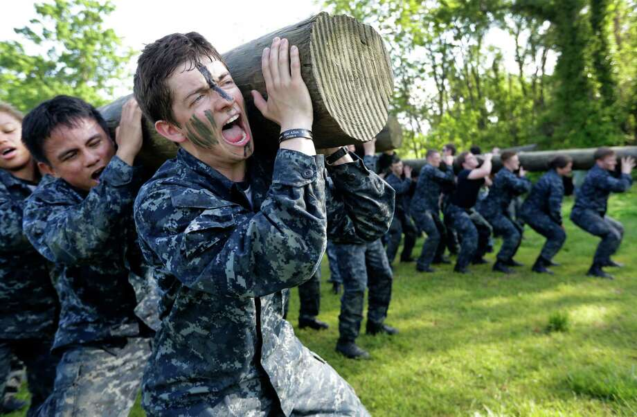 "Phillip Metcalfe of Plano, Tex., screams as he lifts a log during Sea Trials, a day of physical and mental challenges for freshman midshipmen, known as ""plebes,"" that caps off their first year at the U.S. Naval Academy in Annapolis, Md., Tuesday, May 13, 2014. Photo: Patrick Semansky, Associated Press / AP"