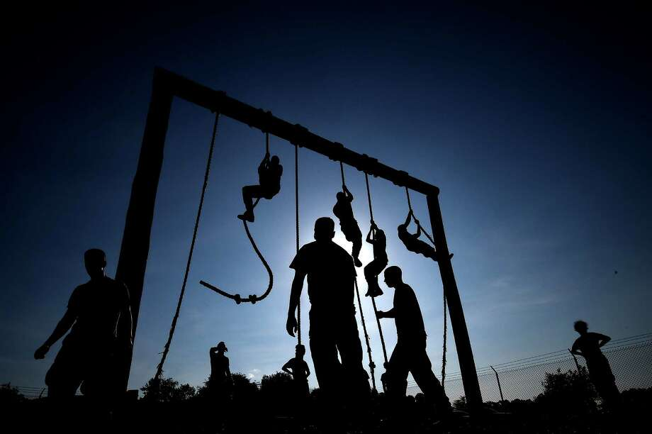 Members of the United States Naval Academy freshman class climb ropes on a obstacle course during the annual Sea Trials training exercise at the U.S. Naval Academy on May 13, 2014 in Annapolis, Maryland. Photo: Patrick Smith, Getty Images / 2014 Getty Images