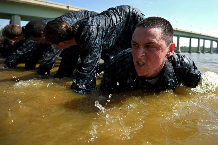 Members of the United States Naval Academy freshman crawl under one another at the wet and sandy station during the annual Sea Trials training exercise at the U.S. Naval Academy on May 13, 2014 in Annapolis, Maryland. Photo: Patrick Smith, Getty Images / 2014 Getty Images
