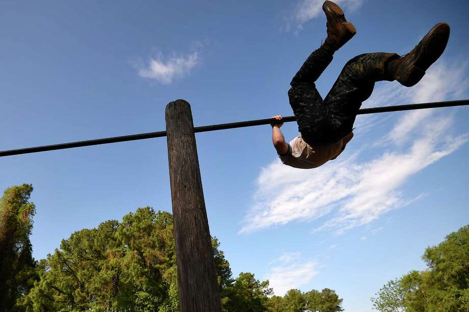 A member of the United States Naval Academy freshman class flips over a bar on a obstacle course during the annual Sea Trials training exercise at the U.S. Naval Academy on May 13, 2014 in Annapolis, Maryland. Photo: Patrick Smith, Getty Images / 2014 Getty Images