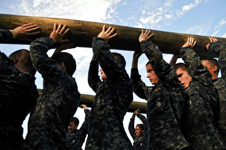 Members of the United States Naval Academy freshman class lift logs during the annual Sea Trials training exercise at the U.S. Naval Academy on May 13, 2014 in Annapolis, Maryland. Photo: Patrick Smith, Getty Images / 2014 Getty Images