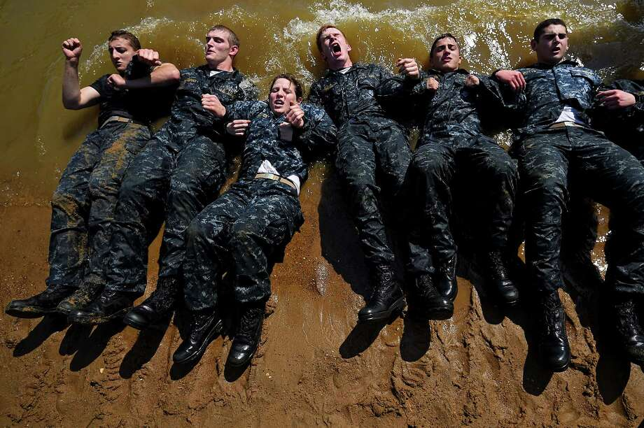 Members of the United States Naval Academy freshman class do sit-ups at the wet and sandy station during the annual Sea Trials training exercise at the U.S. Naval Academy on May 13, 2014 in Annapolis, Maryland. Photo: Patrick Smith, Getty Images / 2014 Getty Images