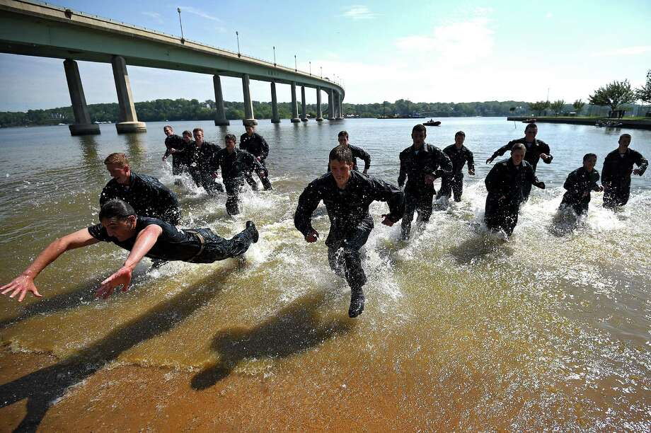 Members of the United States Naval Academy freshman class race to the sand at the wet and sandy station during the annual Sea Trials training exercise at the U.S. Naval Academy on May 13, 2014 in Annapolis, Maryland. Photo: Patrick Smith, Getty Images / 2014 Getty Images