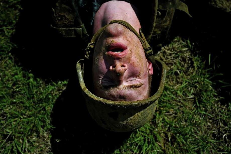 A member of the United States Naval Academy freshman class shows his exhaustion at the wet and sandy station during the annual Sea Trials training exercise at the U.S. Naval Academy on May 13, 2014 in Annapolis, Maryland. Photo: Patrick Smith, Getty Images / 2014 Getty Images