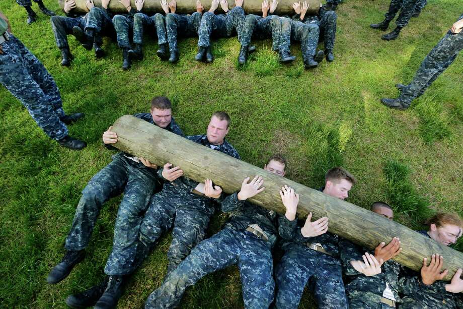 "Freshman midshipmen, known as ""plebes,"" perform sit ups with a log across their chests during Sea Trials, a day of physical and mental challenges that caps off their first year at the U.S. Naval Academy in Annapolis, Md., Tuesday, May 13, 2014. Photo: Patrick Semansky, Associated Press / AP"