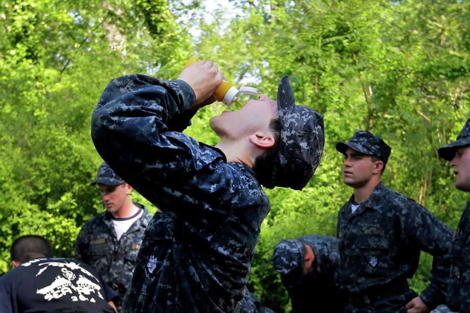 "Jonathan Freel, center, of Houston, eats mustard in an attempt to avoid cramps during a short break in Sea Trials, a day of physical and mental challenges for freshman midshipmen, known as ""plebes,"" that caps off their first year at the U.S. Naval Academy in Annapolis, Md., Tuesday, May 13, 2014. Photo: Patrick Semansky, Associated Press / AP"