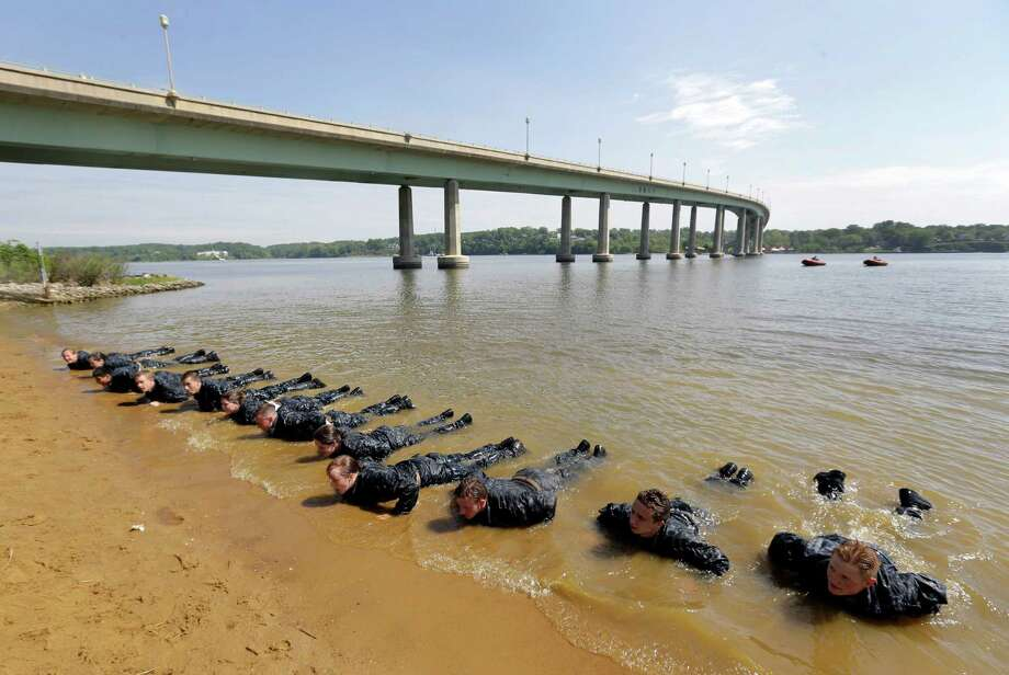 "Freshman midshipmen, known as ""plebes,"" perform push ups on the banks of the Severn River during Sea Trials, a day of physical and mental challenges that caps off the freshman year at the U.S. Naval Academy in Annapolis, Md., Tuesday, May 13, 2014. Photo: Patrick Semansky, Associated Press / AP"