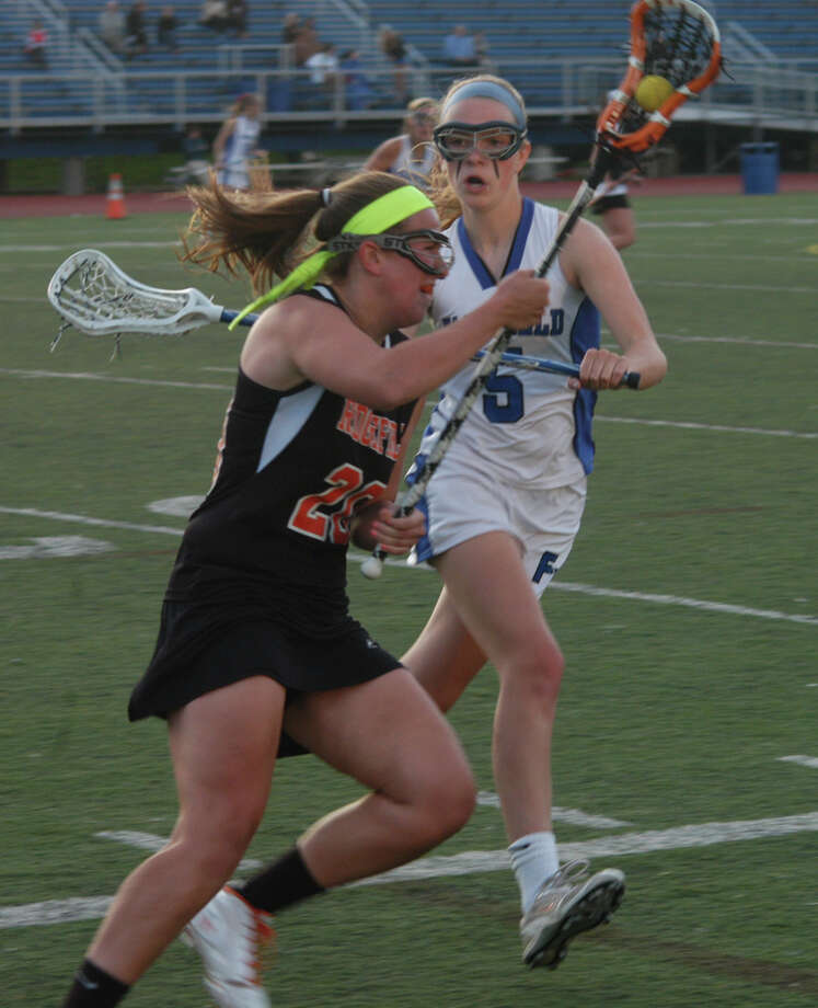 Fairfiled Ludlowe's Sophie Butcher (5) challenges Ridgefield's Erica Ely in an FCIAC girls lacrosse game at Taft Field on Tuesday, May 13. The Falcons won 15-14. Photo: Andy Hutchison, Reid L. Walmark / Fairfield Citizen