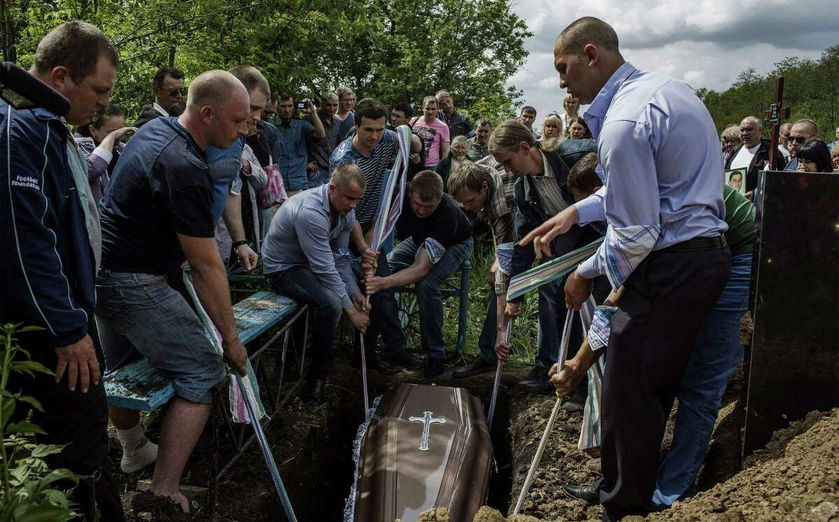 Relatives lower the coffin of a pro-Russian activist who was shot over the weekend by pro-Kiev militants. The killing occurred the day of a referendum vote on independence.