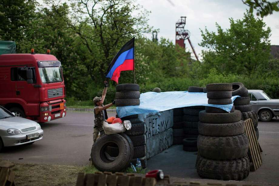 """Pro-Russian insurgents with the self-proclaimed Donetsk People's Republic man a checkpoint by the Karl Marx coal mine seen in the background near Korsun, a small town about 30 km north-east from  Donetsk, eastern Ukraine, Tuesday, May 13, 2014. The words on the wall of barricades read  """" No fascism"""". The Donetsk People's Republic has proclaimed independence from Ukraine after a contentious autonomy referendum Sunday that has been rejected by the government and the international community. (AP Photo/Alexander Zemlianichenko) ORG XMIT: XAZ106 Photo: Alexander Zemlianichenko / AP"""