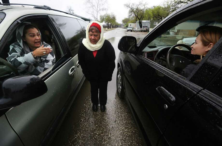 Maria Hernandez (from the left), Elida Rivera and Griselda Valdes have an impromptu meeting as they pick up their kids after school over the possibility of being moved out of their homes. Photo: BOB OWEN, San Antonio Express-News / © 2012 San Antonio Express-News