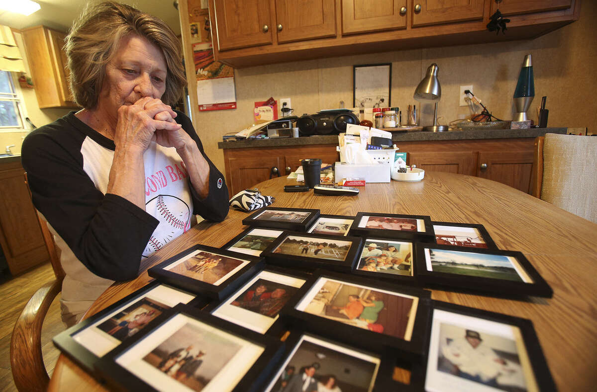 Carolyn Richardson contemplates photos as she looks through photos and documents from her deceased husband Ansom Dale Richardson on May 13, 2014.