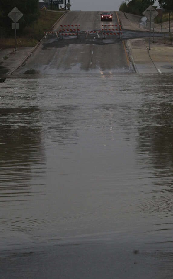 A motorist pauses near debris in the road close to Salado Creek and Interstate 35 after the area flooded from the thunder- storm. Heavy rain caused many San Antonio roads to be shut down late Monday and into Tuesday. Photo: John Davenport / San Antonio Express-News / ©San Antonio Express-News/John Davenport