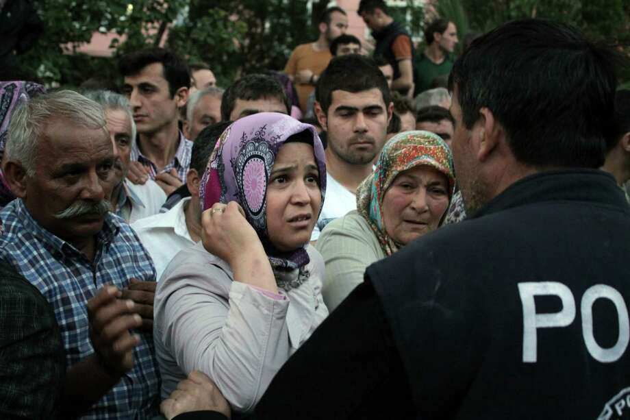 Relatives try to get information outside a local hospital after an explosion and fire at a coal mine in Soma, in western Turkey, Tuesday, May 13, 2014.  An explosion and fire at a coal mine in western Turkey killed at least one miner Tuesday and left up to 300 workers trapped underground, a Turkish official said. Twenty people were rescued from the mine in the town of Soma in Manisa province but one later died in the hospital, Soma administrator Mehmet Bahattin Atci told reporters. The town is 250 kilometers (155 miles) south of Istanbul. (AP Photo/Depo Photos) Photo: STR / Depo Photos