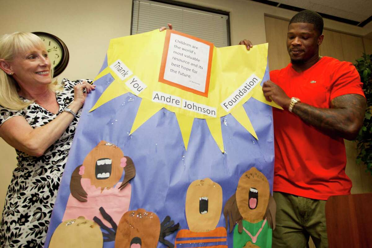 """Rebecca White, president and CEO of the Houston Area Women's Center, and Houston Texans wide receiver Andre Johnson hold up a thank you poster after Johnson donated $30,000 to the center this spring. Johnson has said he'd like to help those abused women get their GEDs and advice in career development. The athlete who was raised by his single mom recently asked on a daytime talk show, """"What are we without our mothers?"""""""