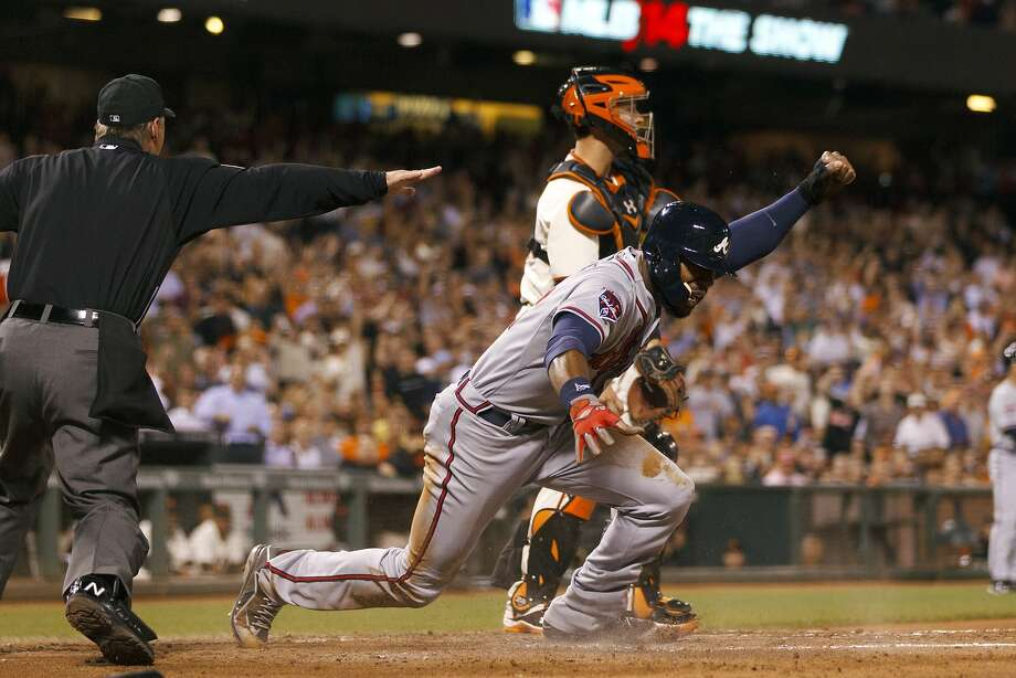 The Braves' Jason Heyward (foreground) slid under the tag of Buster Posey in the sixth. Photo: Jason O. Watson, Getty Images
