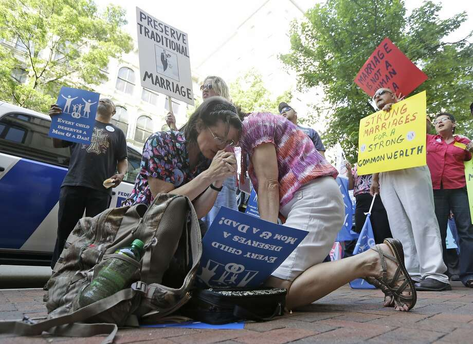 Members of the Family Foundation and supporters of traditional marriage, Barbara Kerns, of Midlothain, Va., left, and Linda Gagliardo, of Chester Va., pray outside the Federal Appeals Court in Richmond, Va., Tuesday, May 13, 2014. The 4th U.S. Circuit Court of Appeals in Richmond is taking up the issue of gay marriage, with arguments scheduled on a ruling that the state's ban on such unions is unconstitutional.  (AP Photo/Steve Helber) Photo: Steve Helber, Associated Press