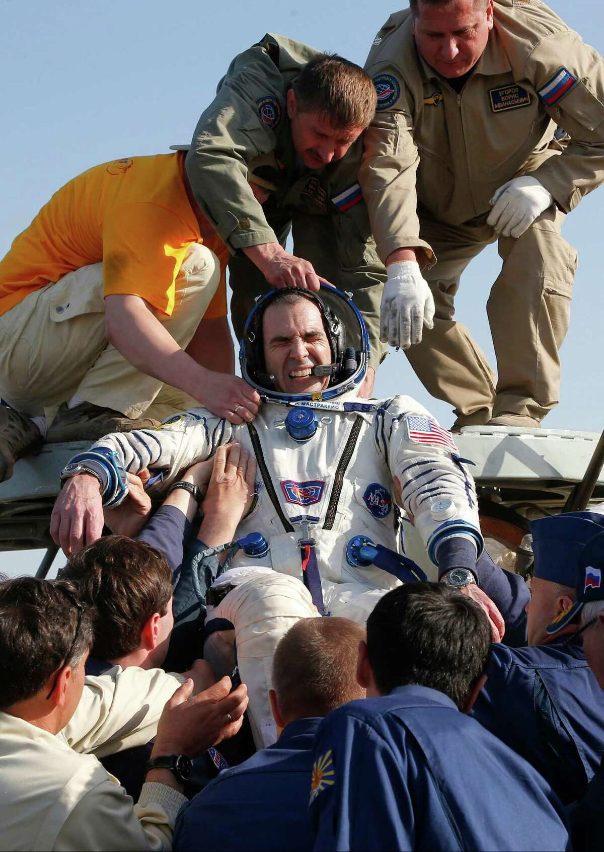 A Russian space agency rescue team helps U.S. astronaut Rick Mastracchio, a Waterbury, Conn. native, to get off the capsule of the Russian Soyuz TMA-11 module shortly after the landing, about 150 kilometers (93 miles) southeast of the Kazakh town of Dzhezkazgan, Kazakhstan, Wednesday, May 14, 2014. The Soyuz space capsule with Mastracchio, Japanese astronaut Koichi Wakata and Russian cosmonaut Mikhail Tyurin, returning from a five-month mission to the International Space Station landed safely Wednesday on the steppes of Kazakhstan. (AP Photo/Dmitry Lovetsky, pool)
