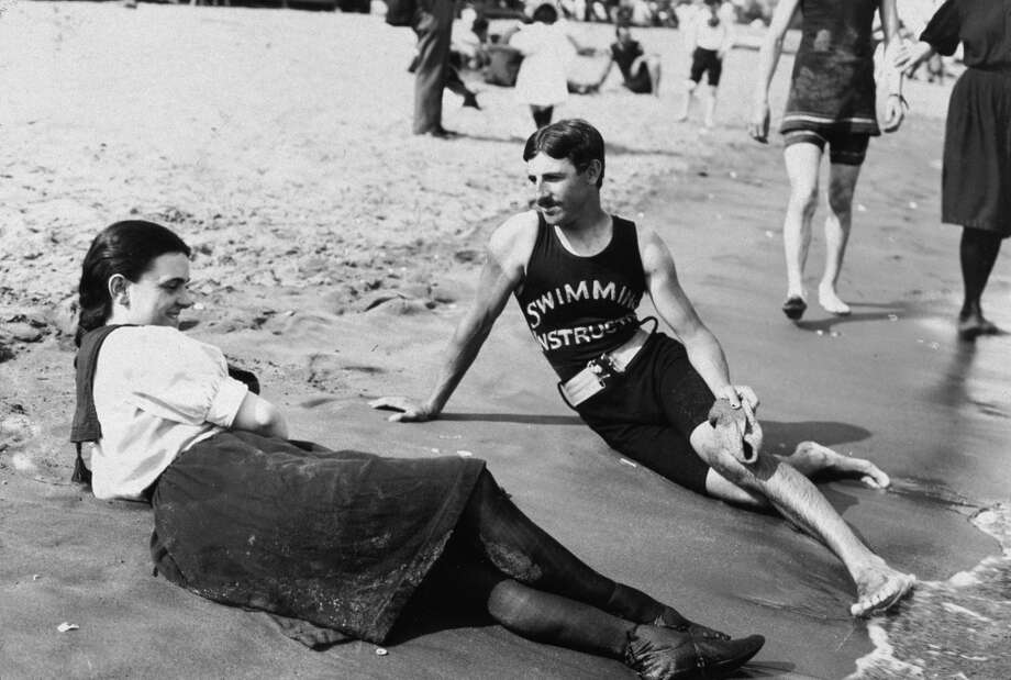 Portrait of a bathing suit-clad woman and a swimming instructor lying close to the surf on Midland Beach, Staten Island, New York, 1898. Photo: Museum Of The City Of New York/B, Getty Images