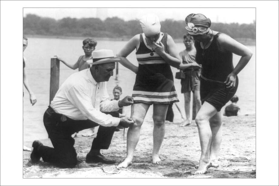 Enforcement of the bathing suit rules circa 1922 in the U.S. The rules stated that suits should be no more than six inches above the knee. Photo: Buyenlarge, Getty Images