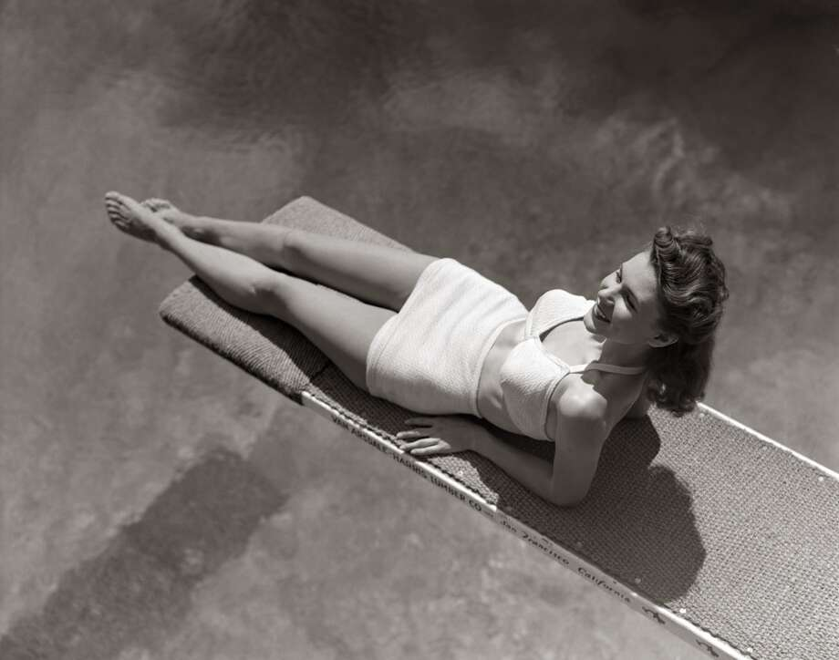 A woman lounges on a diving board in a two-piece bathing suit, circa 1940s. Two-piece swimsuits made an appearance prior to the bikini, but for good measure belly buttons remained covered. Photo: H. Armstrong Roberts, Retrofile/Getty Images