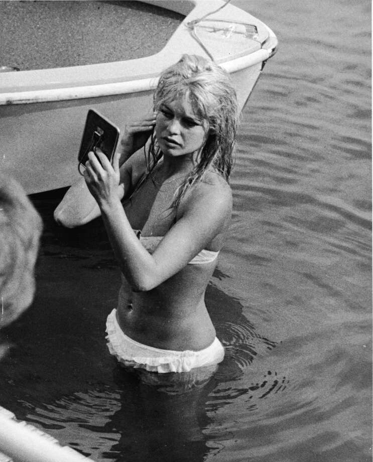 French actor Brigitte Bardot looks at her reflection in a mirror, while standing in the waters of Lake Leman, June 13, 1961. Photo: Express Newspapers, Getty Images