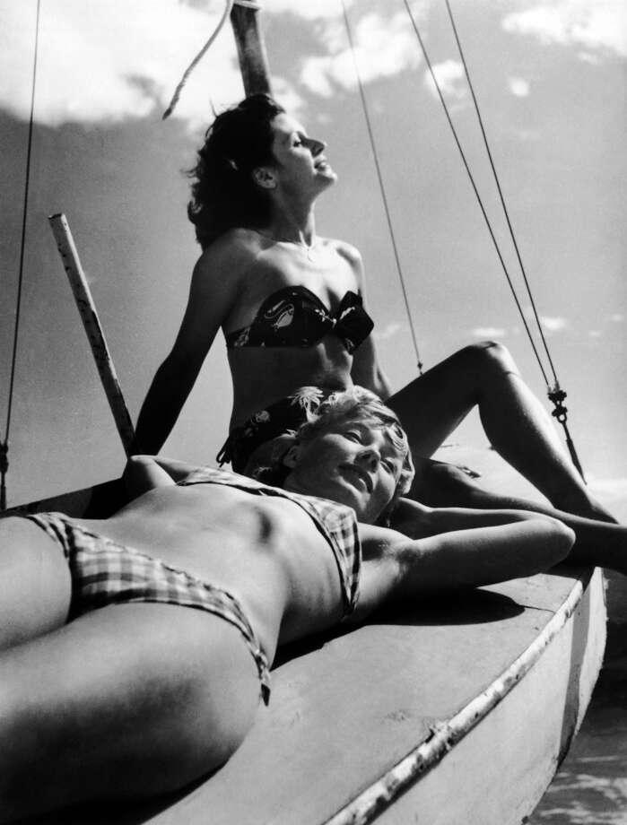 Two girls sunbathe on a sailboat, date unknown. Photo: Keystone-France, Gamma-Keystone Via Getty Images