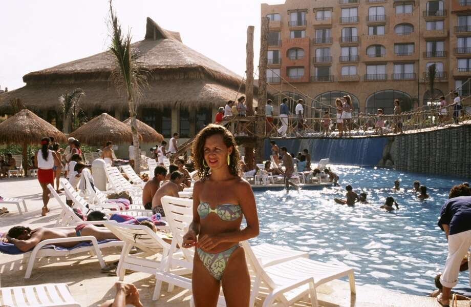 A woman in a classic '80s-style bikini poses next to a resort pool in this 1989 Cancun, Mexico photo. Photo: George Rose, Getty Images