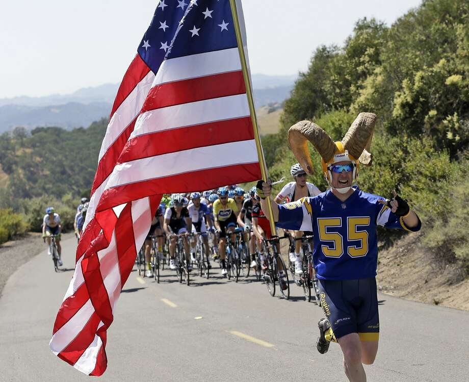 A fan runs with a U.S. flag in front of the peloton during Stage 3 of the Tour of California cycling race, Tuesday, May 13, 2014, at Mount Diablo State Park in Clayton, Calif. (AP Photo/Marcio Jose Sanchez) Photo: Marcio Jose Sanchez, Associated Press