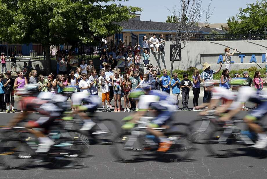 Children wave at riders who pedal past Altamont Creek Elementary School during Stage 3 of the Tour of California cycling race, Tuesday, May 13, 2014, in Livermore. Photo: Marcio Jose Sanchez, Associated Press
