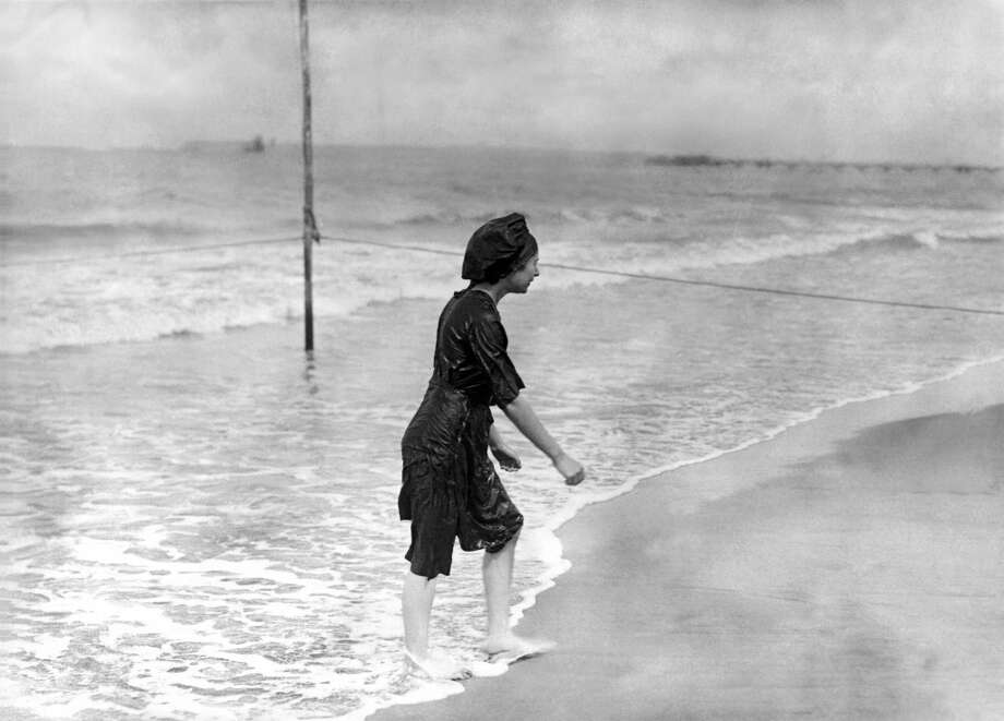 A woman exits from the ocean in a bedraggled looking bathing suit, France, circa 1905. Photo: Underwood Archives, Getty Images